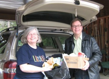 Leslie R and Pastor Brian loading Leslie's car with boxes of mugs and craft supplies that were ready for delivery.