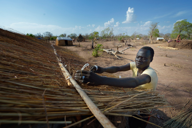 Deng Majok Makir puts a roof on a temporary shelter for his family near Ajoung Thok, South Sudan. Credit: ACT/Paul Jeffrey