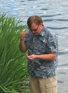 Is Pastor Brian blessing a baby frog or is his biology background sparking curiosity?
