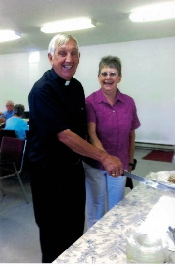 Rev. Keith Peterson  and Leslie Stirling show their smiles as he gets ready to cut the cake as part of the celebration of his 40th anniversary of ordination.