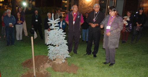 Bishop Lydia Mamakwa (foreground, right) speaks before the planting of a symbolic evergreen tree at the end of the 2015 Sacred Circle, as Diocesan Bishop of Missinipi Adam Halkett (foreground, left) and Anglican Council of Indigenous Peoples co-chair Sid Black (foreground, centre) listen. ~ source:  Anglican Church of Canada website