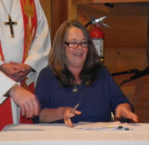 Susan delighted as she completes the signing of the documents.