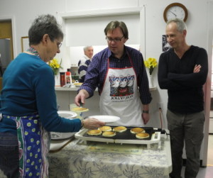 """I suppose so,"" Leslie replied.  Pastor Brian serves up a pancake, with Keith and Jerry enjoying the exchange."