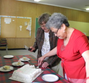 Betty and Norma cutting cake